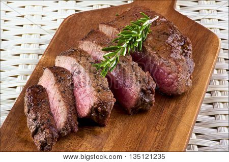 Slices of Delicious Roast Beef Medium Rare with Rosemary on Wooden Cutting Board closeup on Wicker background