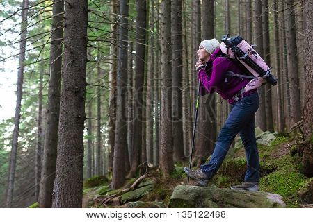 Female Hiker Staying inside Deep Old Forest on Moss Stone with Backpack and Trekking Pole Looking into Distance with Pensive Face