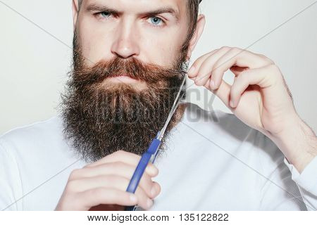 handsome young man hairdresser with long beard and moustache on serious face holding scissors on grey background in studio