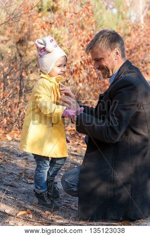 Father Helping Little Baby Daughter to Wear Coat on Walk in Autumnal Park