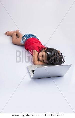 indian little girl feeling sleepy using laptop, asian small girl playing on laptop, isolated over white background, cute indian baby girl lying on floor playing on laptop
