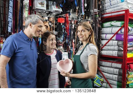Saleswoman Showing Heart Shape Food Bowl To Father And Daughter