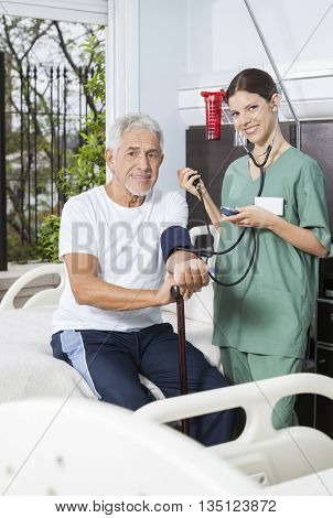 Smiling Nurse Checking Blood Pressure Of Patient In Rehab Center