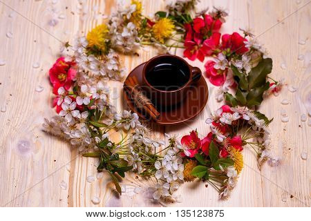 Cup of coffee with cinnamon sticks and beautiful spring flowers blossom wreath on wooden background
