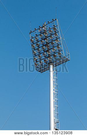 Closeup of a stadium lights with blue sky.