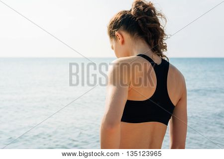 Athletic Girl With Curly Hair In A Sports Bra Standing On The Shore And Looking At The Water At Sunr