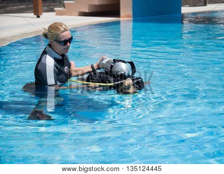 Paliouri Greece - June 15 2016: Young woman tries a scuba dive in a pool with an instructor.Scuba diving is a fun sport enjoyed by many people.