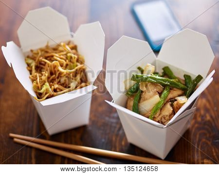 chinese take out in boxes with chopsticks and phone in background
