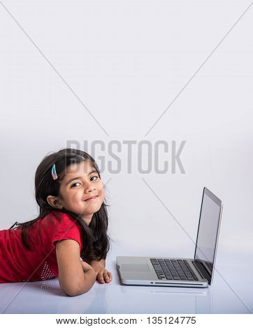 cheerful indian little girl using laptop, asian small girl playing on laptop, isolated over white background, cute indian baby girl lying on floor playing on laptop