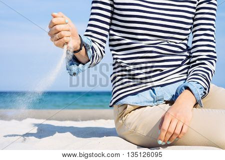 Close-up Of A Girl In A Striped T-shirt On The Beach Which Scatters Sand On The Wind