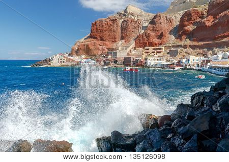 Big waves in water area the old harbor Oia village.