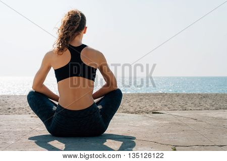 Athletic Girl With Curly Hair In A Sports Bra Sitting On A Beach And Looks At Sea In The Morning