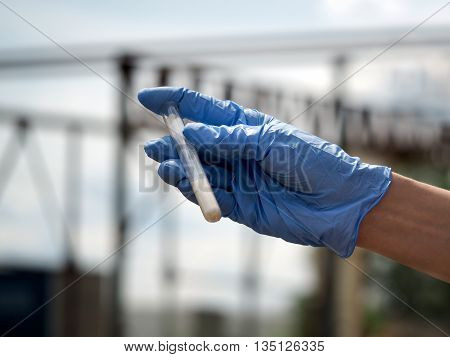 Hand in glove holding a test tube with a dry substance. Background sky plant construction