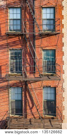 City brick apartment building with fire escape.