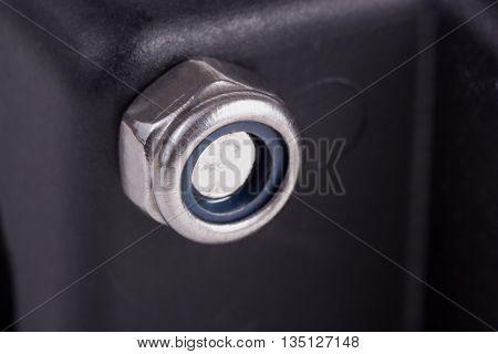 Single metal self-locking nut on the black plastic surface