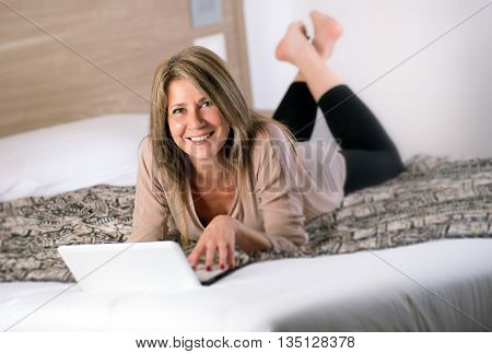 Gorgeous Mature Woman Laying On Bed With Laptop