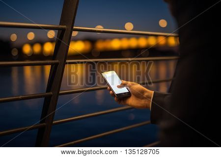 Close up of a man sending an sms on a mobile phone.