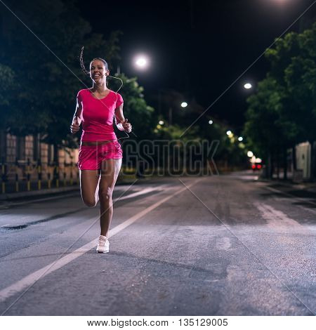 Woman running outdoors on the night. High ISO.