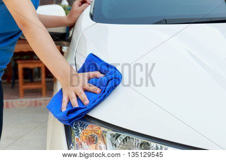 Woman hands cleaning white car using microfiber cloth concept