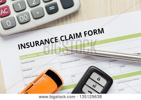 Top view of insurance claim form with car key car toy and calculator on wooden desk.