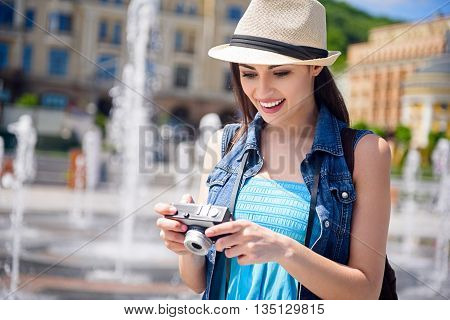 Cheerful female tourist is making journey across city. She is holding a camera and looking at photos with joy. Woman is standing and smiling