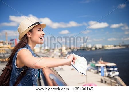 Happy female tourist is enjoying scenery of river in city. She is leaning on the border and smiling. Woman is standing and holding a map