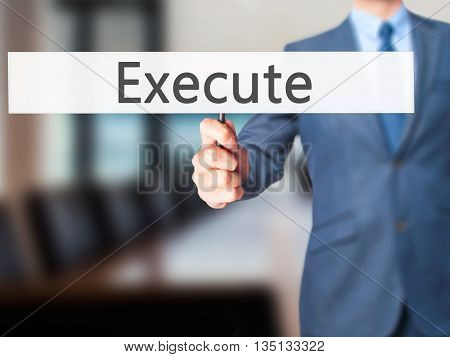 Execute - Businessman Hand Holding Sign