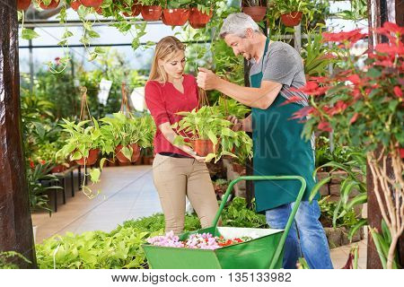 Woman getting quaity consultation from gardener in a garden center