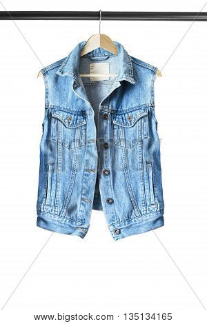 Blue denim vest on wooden clothes rack isolated over white