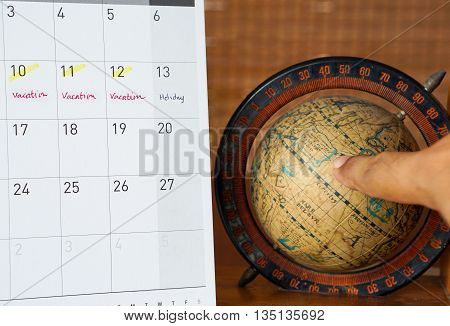 calendar with vacation remark and vintage global map with finger point to the map