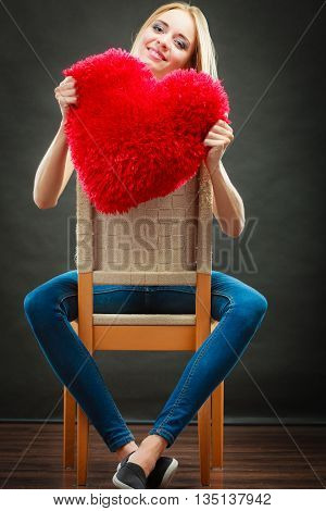 Valentines day love and relationships concept. Blonde long hair young woman holding heart shaped pillow love symbol on dark background