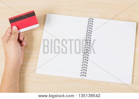 hand holding credit card and put notebook on wood table