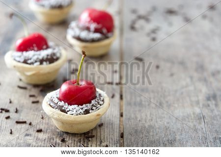 Delicious chocolate tartlets with one cherry and coconut on a wooden table