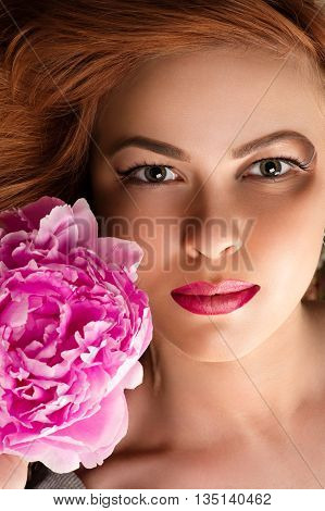 attractive woman with bright makeup with pink peony