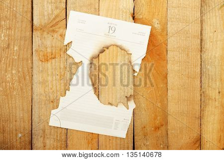 Burnt paper with a calendar on the wooden background