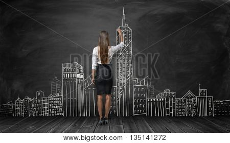 Back view of businesswoman drawing city-sketch on black background. Implementation of the idea. creative process. Design of architectural project. Business staff. Realize the dream.
