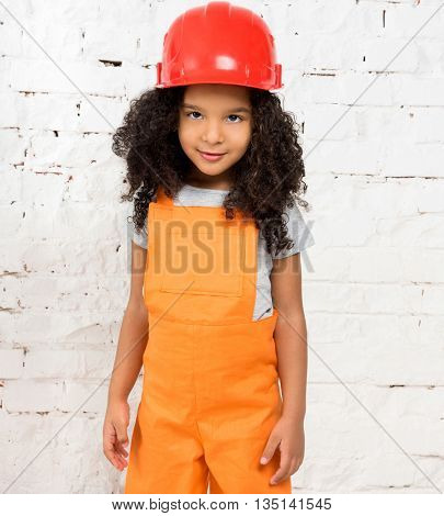 cute little girl in orange repairmen uniform and helmet