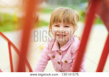 little beautiful smiling girl on playground outside