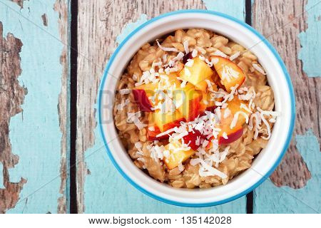 Bowl Of Overnight Breakfast Oats With Diced Peach And Coconut, Overhead View On Rustic Blue Wood