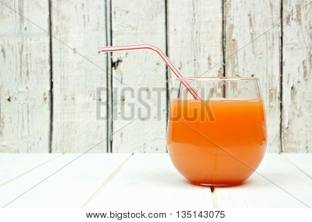 Glass Of Grapefruit Juice With Straw On A Rustic White Wooden Background