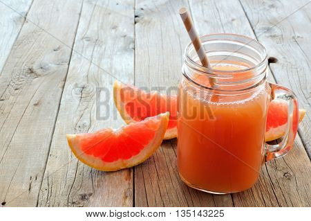 Mason Jar Glass Of Grapefruit Juice With Fruit Slices And Straws On Rustic Wooden Background