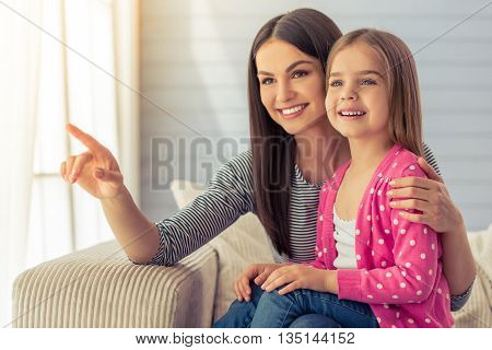 Beautiful young mother and her cute little daughter are smiling pointing and looking away sitting on sofa at home