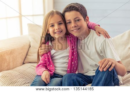 Cute little girl and her brother are hugging looking at camera and smiling sitting on sofa at home