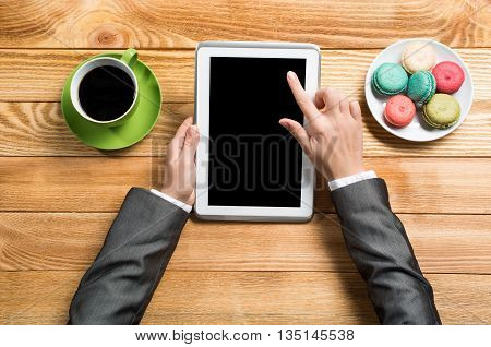 Top view of female hands using tablet device while sitting at wooden table