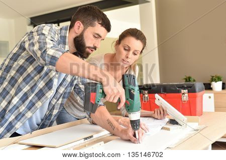Couple assembling new furniture