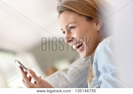 Cheerful woman using smartphone relaxed on sofa