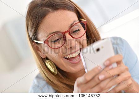 Cheerful girl having fun using smartphone