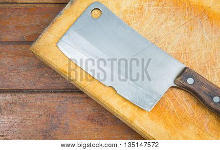 cutting board and old meat cleaver on wooden background