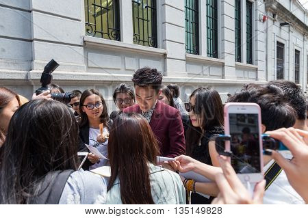 MILAN ITALY - JUNE 18: Famous Chinese actor signs autographs outside Marni fashion show building for Milan Men's Fashion Week on JUNE 18 2016 in Milan.