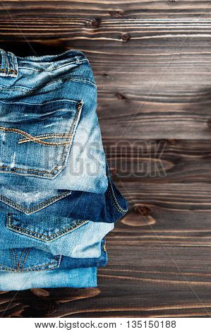 stack of various shades of blue jeans on a wood background